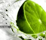 Imagem de um limão verde caindo na água, que causa respingos