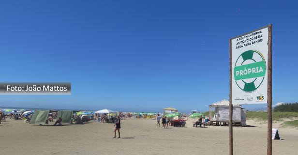 Foto de João Mattos mostra a praia de Atlântida com céu azul, pessoas na orla e placa de balneabilidade
