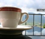 Xícara de café sobre uma mesa, com um fundo de morros e céu nublado