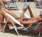 Mulher de biquíni lê um livro à beira-mar, deitada de costas em sua cadeira de praia