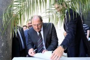 Governador assina um documento em meio às árvores do jardim do Palácio Piratini