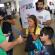Crianças vestidas de super-heróis distribuem panfletos no aeroporto sobre o aedes. A ação é do Simers