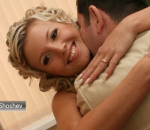 Casamento. Noiva recebe um abraço de um homem e sorri para a câmera