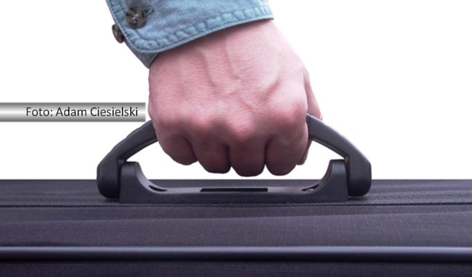 Detalhe de uma mão masculina segurando a alça de uma mala