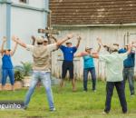 Pessoas em círculo fazendo exercício físico ao ar livre em frente a uma igreja