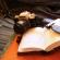 Bloco de anotações está sob uma câmera fotográfica. Atrás tem uma bolsa de equipamentos de jornalista