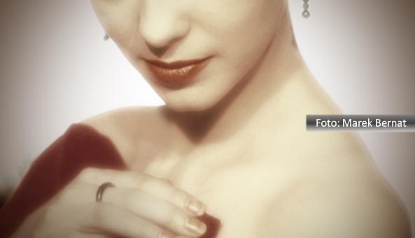 Imagem de mulher sexy, onde aparece parte do nariz e brinco, a boca e as mãos. Usa roupa vermelha de uma manga só.