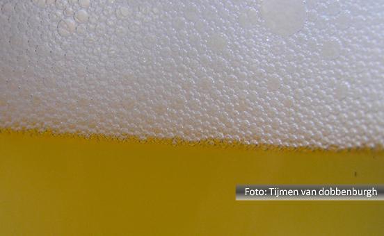 Detalhe do chope em um copo e bastante espuma sobre ele.