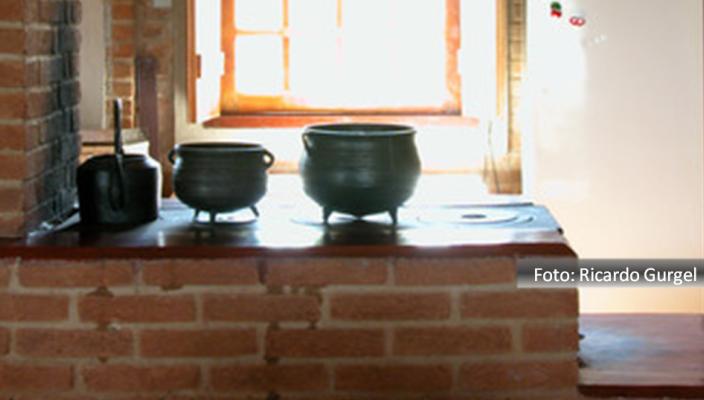 Cheleira e duas panelas de ferro sobre fogão montado em bancada de pedra