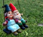 Casal de gnomos andando de balanço em um gramado