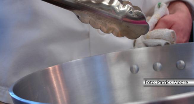 Detalhe de mão de chef segurando um pegador de massa na parte superior de uma panela