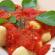 Prato de nhoque com molho vermelho e folhas de manjericão