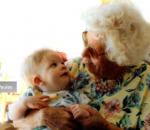 Avó sentada com um bebê no colo e os dois olhando fixamente para os olhos do outro