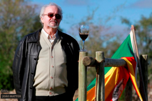 Jornalista Danilo Ucha ao lado de uma porteira com um taça de vinho e a bandeira do Rio Grande do Sul. Foto de João Mattos
