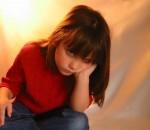 Menina sentada com cara de entediada ou emburrada