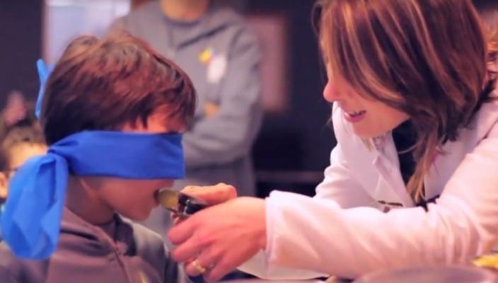 Mãe dando uma prova de alimento para uma criança com venda nos olhos