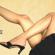 Pernas femininas para o ar, em pose sensual, um pé calçando uma sandália e aparecendo uma parte da saia curta
