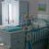 Quarto de bebê em que aparece o berço, com enfeites e brinquedos pendurados, com roupeiro e gaveteiro