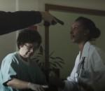 Médica e enfermeiras prestando atendimento em hospital com uma arma apontada para o rosto de uma delas