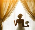 Noiva segurando um ramalhete em frente à janela