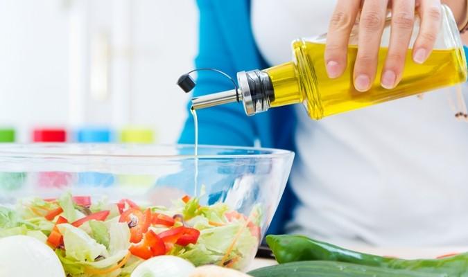 Detalhe de óleo sendo colocado em salada foto Freepik