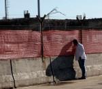 Homem espia pelo tapume do aeroporto Salgado Filho. Foto: JOão Mattos Fotografia