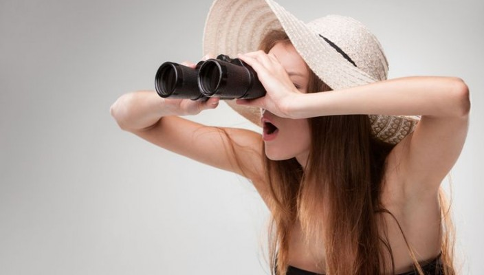 Young woman in hat looking through binoculars on gray background. Travel and adventure concept. Closeup.